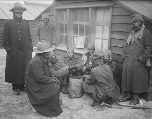 SANLC men round a brazier at their camp